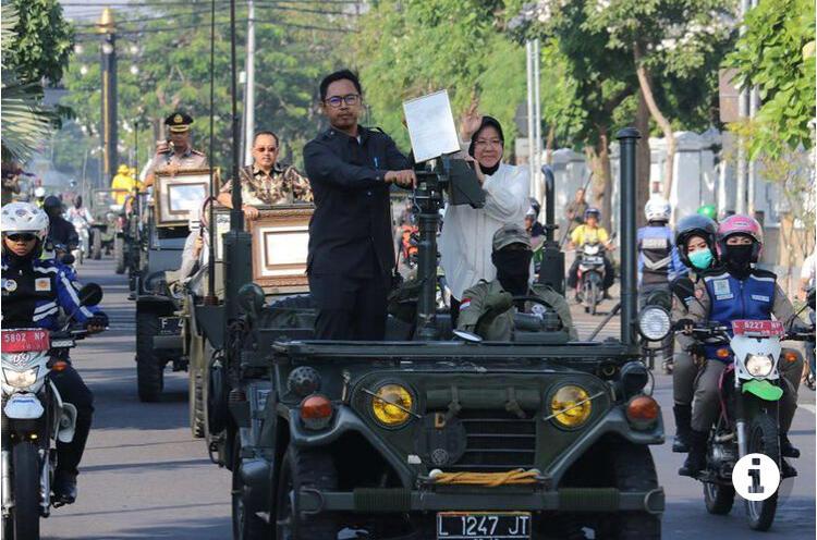 SURABAYA, KOMPAS.com - Wali Kota Surabaya Tri Rismaharini mengarak piagam penghargaan