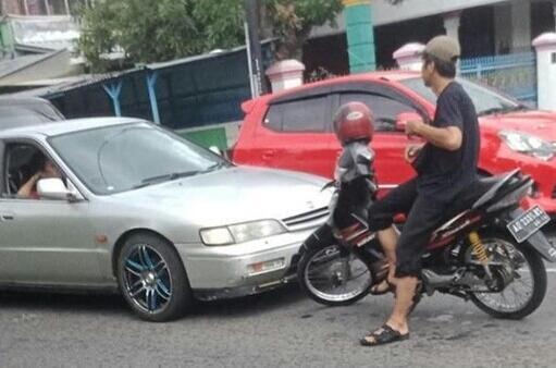 Seorang Pengendara Duduk Santuy di Atas Motornya di Tengah Jalan! Sedang Apa Dia Ya?